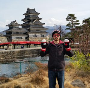 Isaya standing in front of a Japanese castle